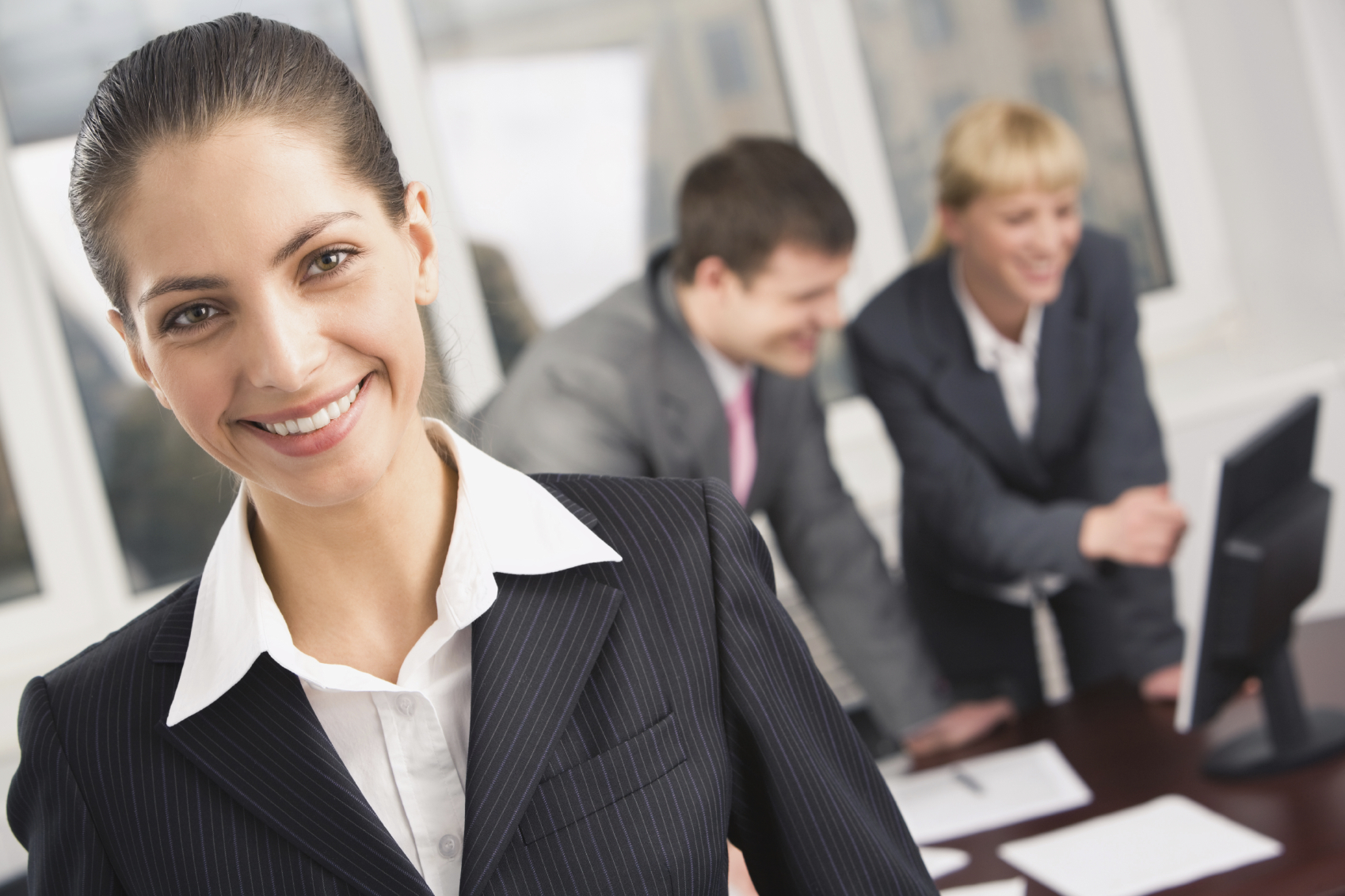 professionally dressed individuals in an office meeting room