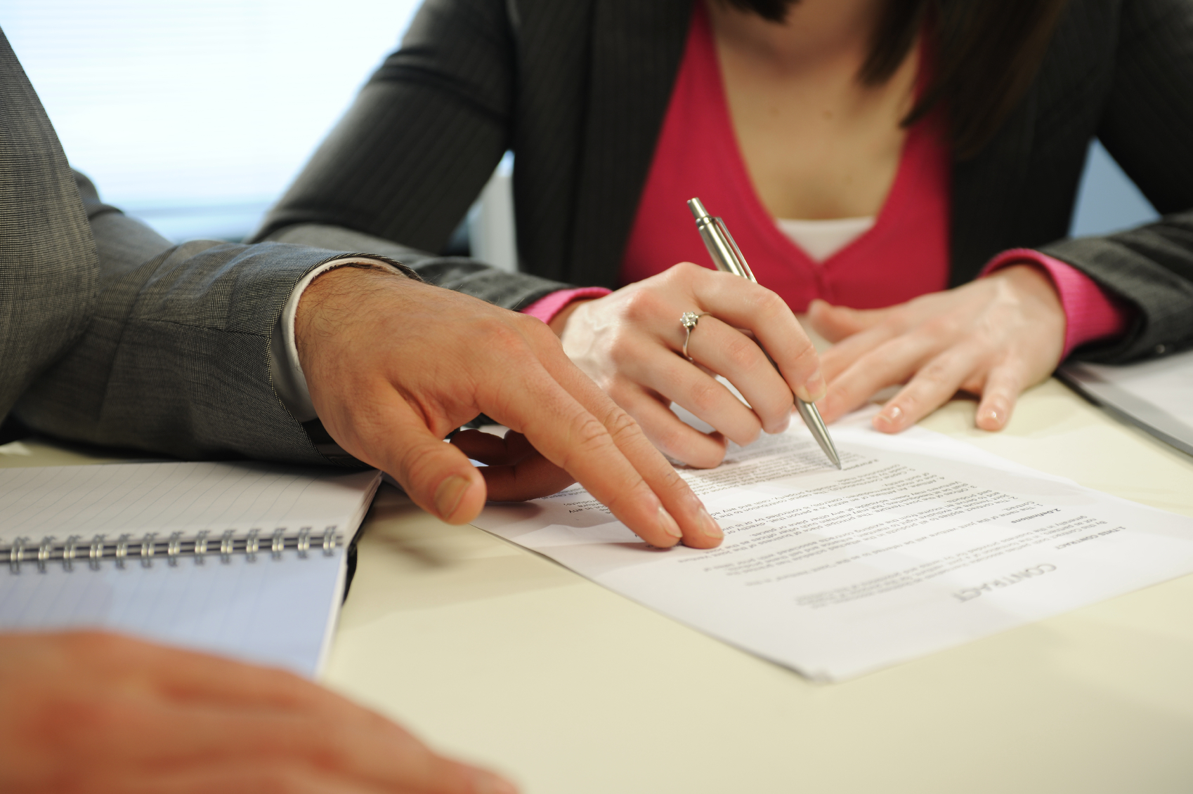 a man and woman signing papers
